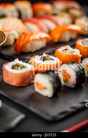 Sushi set rolls served on stone slate - Stock Photo