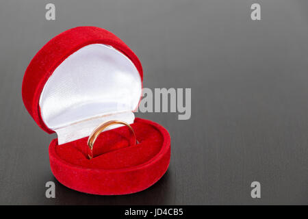 Wedding ring in a red box lie on the surface of the black table - Stock Photo