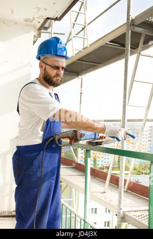 An upset construction worker in a work outfit and in a protective helmet shows a finger. Work on high scaffolding - Stock Photo
