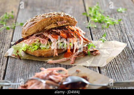Street food: Barbecue pulled pork wholemeal sandwich with coleslaw, hot BBQ sauce served on brown wrapping paper - Stock Photo
