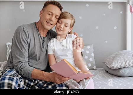 Affectionate charming father hugging his little girl - Stock Photo