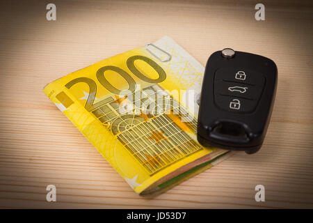 Close up of car key on pile stack of euro banknotes on the table. Credit, finance, renting and leasing concepts. - Stock Photo