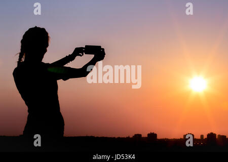 Silhouette of female taking photos of sunset with smart phone. Summer, travel and technology concepts. - Stock Photo