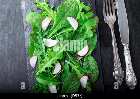 Mixed salad leaves with radish on black slate plate. Top view - Stock Photo