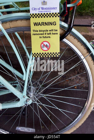Council warning notice on bicycle about removal - Stock Photo