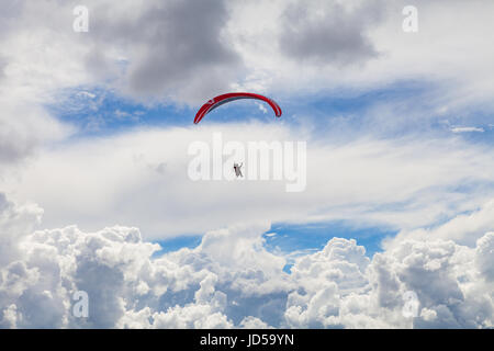 Paragliding in the massive cloudy sky - Stock Photo
