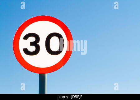 Left sided thirty miles per hour speed limit sign against blue sky with copyspace - Stock Photo