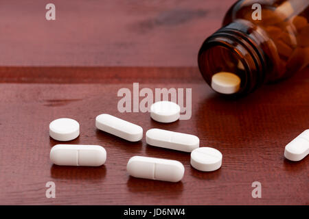 Brown pills bottles and heap of white pills on wooden table - Stock Photo