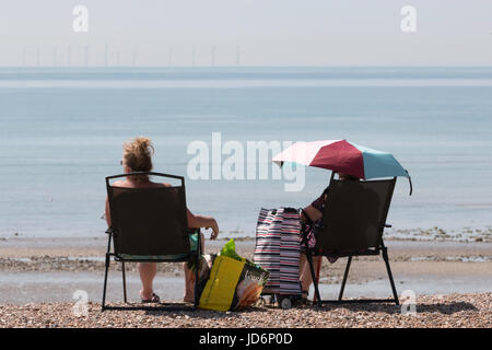 Two Ladies Enjoying the Summer Sun at the Seaside.  One is Seated Under an Umbrella.  An Offshore Wind-Farm Can - Stock Photo