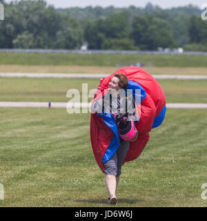 Woman smiles into the wind after a successful skydive - Stock Photo