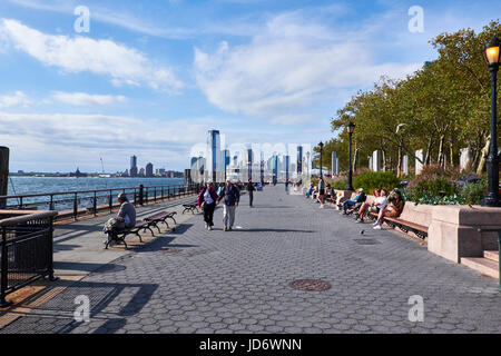 NEW YORK CITY - SEPTEMBER 26, 2016: People strolling and sitting on benches at Battery Park on the south tip of - Stock Photo