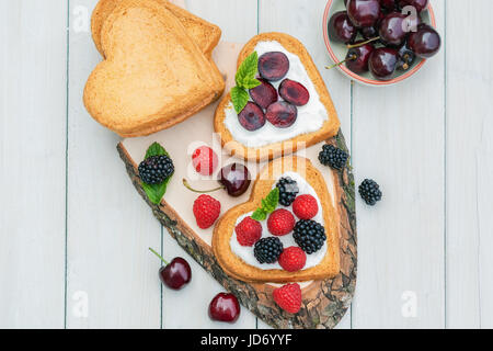 Bowl filled with cherries and heart shaped biscuits spread with quark,  cherries and a twig of mint presented on - Stock Photo