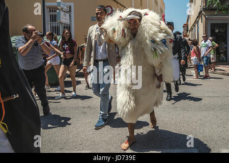 Ciutadella, Menorca. June 18th, 2017: A young man clad in a sheepskin, the 's'Homo des Be' (sheepman), carries a - Stock Photo
