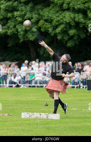 Aberdeen, Scotland - Jun 18, 2017: A competitor in the stone putting event at the Highland Games in Aberdeen, Scotland. - Stock Photo