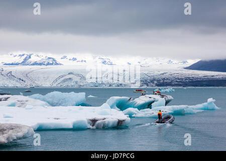 Tour boat operators and patrol boats amid icebergs on the Jokulsarlon glacial lagoon - Stock Photo