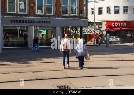 NOTTINGHAM, ENGLAND - JUNE 17: Mother and daughter walking towards Starbucks/Costa coffee shop. In Nottingham, England. - Stock Photo