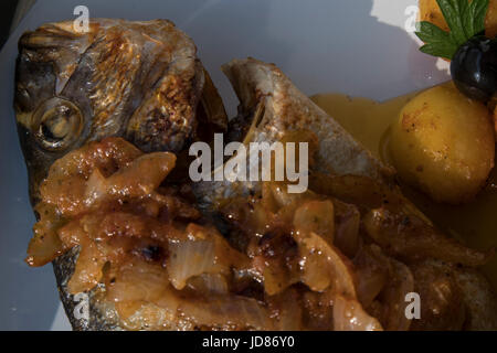 Fish baked in the oven, golden with boiled potatoes and olives in white dish. Typical Portuguese dish. - Stock Photo