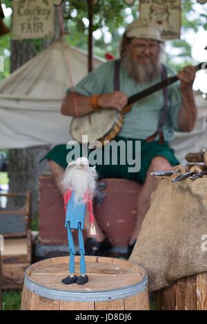 A woodworker playing a banjo and working a wooden puppet at the Hennepin County Fair in Corcoran, Minnesota, USA. - Stock Photo