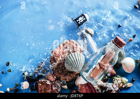 Pirate message in a glass bottle in shallow water with ripple of seawave. Underwater still life. - Stock Photo