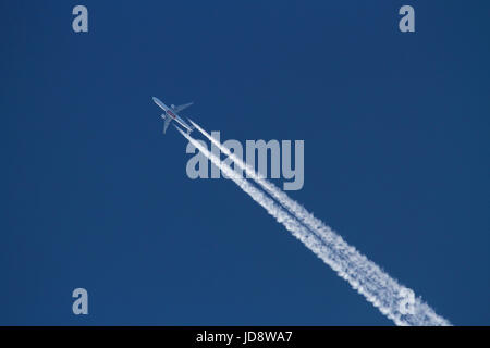 Air travel and the environment. Emirates Boeing 777 passenger jet plane flying at altitude against a blue sky and - Stock Photo