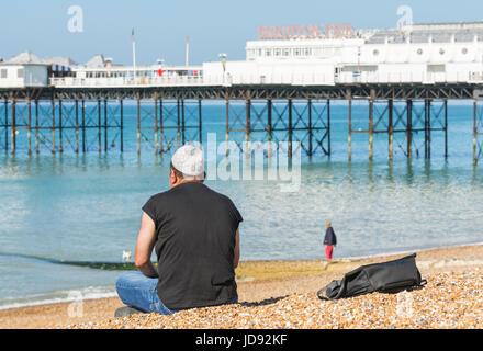 Man wearing a Muslim Taqiyah prayer cap, sitting along on Brighton Beach near Brighton Pier on a sunny day. - Stock Photo