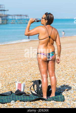 Summer concept. Summer drink. Very tanned woman in bikini having a drink of water on the beach on a hot Summers - Stock Photo