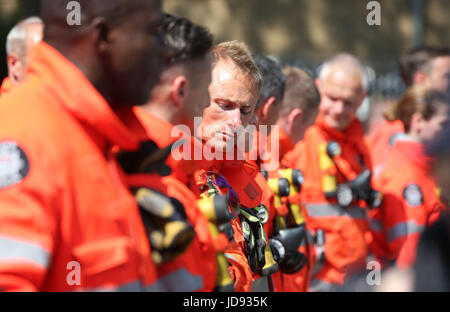 Members of the emergency services gather to observe a minute's silence near to Grenfell Tower in west London after - Stock Photo
