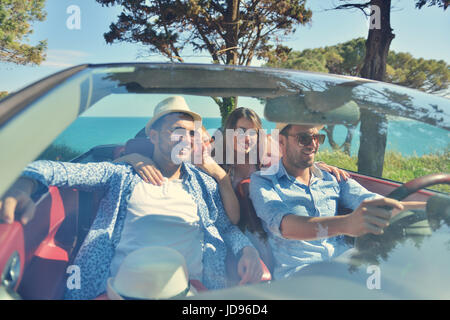 leisure, road trip, travel and people concept - happy friends driving in cabriolet car along country road - Stock Photo