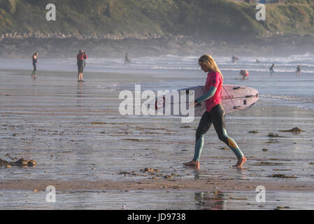 A female surfer walking out of the sea at Fistral Beach in Newquay, Cornwall - Stock Photo