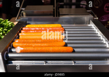 Appetizing barbecued sausages are prepared for hot dogs at food festival - Stock Photo