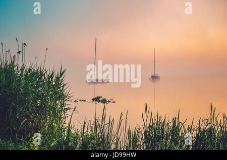 Morning foggy lake landscape. Boats on the lake. - Stock Photo