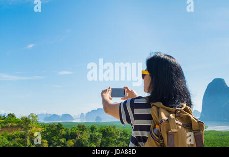 Young traveler woman backpacker use mobile phone take a photo of beautiful of nature at top of mountain and sea - Stock Photo