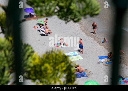 Bathers and sunbathers on the beach seen from the Balcon de Europa, Nerja, Costa del Sol, Spain. - Stock Photo