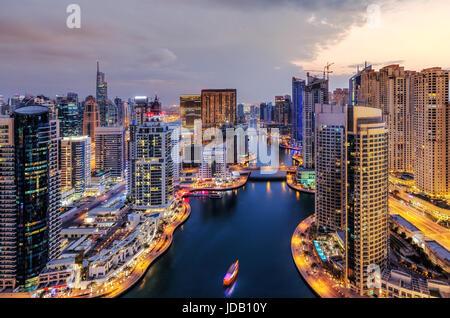 Spectacular view of a big modern city at night. Dubai Marina creek with skyscrapers. Scenic nighttime skyline. Popular - Stock Photo