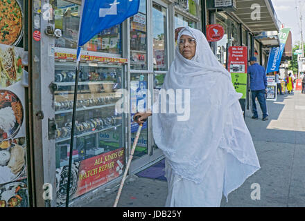 An elderly Muslim woman in traditional dress walking down the street with the aid of a cane. In Jackson Heights - Stock Photo
