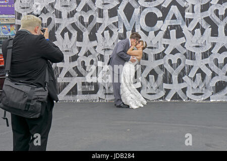 A couple have their wedding photos taken in front of one of the Coney Island Art Walls in Coney Island, Brooklyn, - Stock Photo