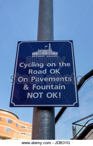 Cycling On The Road OK, On Pavements & Fountain NOT OK! sign on a post in Brewery Square, Dorchester, Dorset - Stock Photo