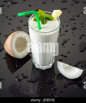 Milkshake with coconut on a black background with drops of water - Stock Photo