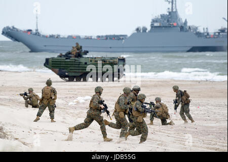 An American Assault Amphibious Vehicle AAV-7 on the beach and Polish minelayer-landing ship ORP Krakow during the - Stock Photo