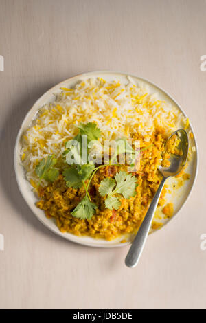 One plate of vegan lentil curry with basmati rice, topped with fresh coriander leaves,  on a light wooden background - Stock Photo