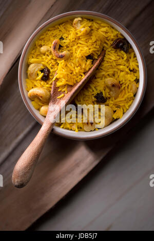 Turmeric rice made with ground turmeric, basmati rice, raisins and cashew nuts, on a light brown background. View from above, soft focus.