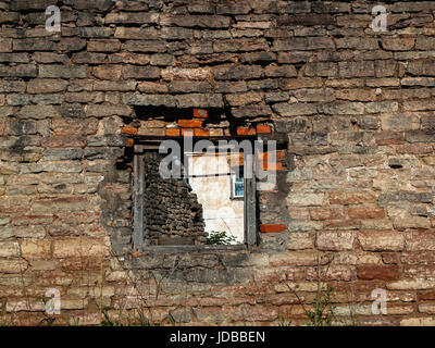 Brick wall of the old destroyed house with textured bricks with an opening in which you can see the window of a - Stock Photo