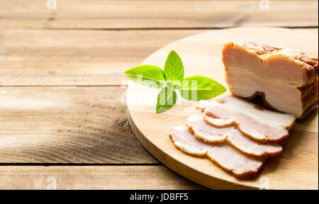 Raw smoked bacon slices on wooden board which herbs - Stock Photo