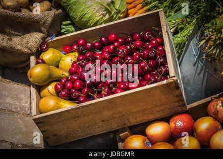 A display box of cherries and pears surrounded by various fruit and vegetables - Stock Photo