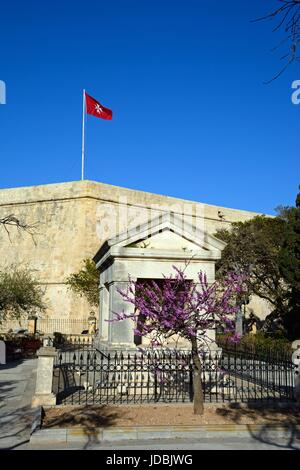 Maltese flag on top of St Johns Cavalier building with a memorial in the foreground in Hastings Gardens, Valletta, - Stock Photo