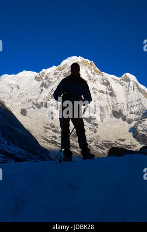 Silhouette of a tourist hiker on Annapurna South Peak Mountain, Nepal. - Stock Photo