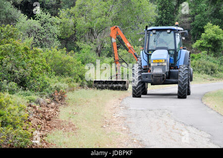 Forester clears weeds from a fire path in a orest. Photographed in Israel - Stock Photo
