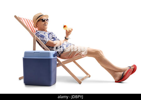 Elderly tourist with a cocktail sitting in a deck chair next to a cooling box isolated on white background - Stock Photo