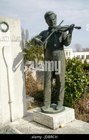 Statue of a man playing the violin on a grave in a cemetery - Stock Photo
