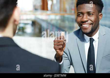 Portrait of young successful African-American businessman smiling and showing thumbs up while talking to partner, - Stock Photo